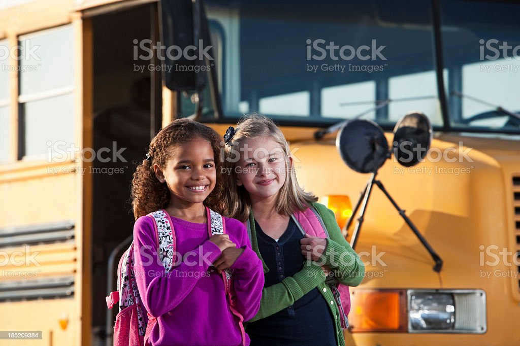 Girls in front of school bus stock photo