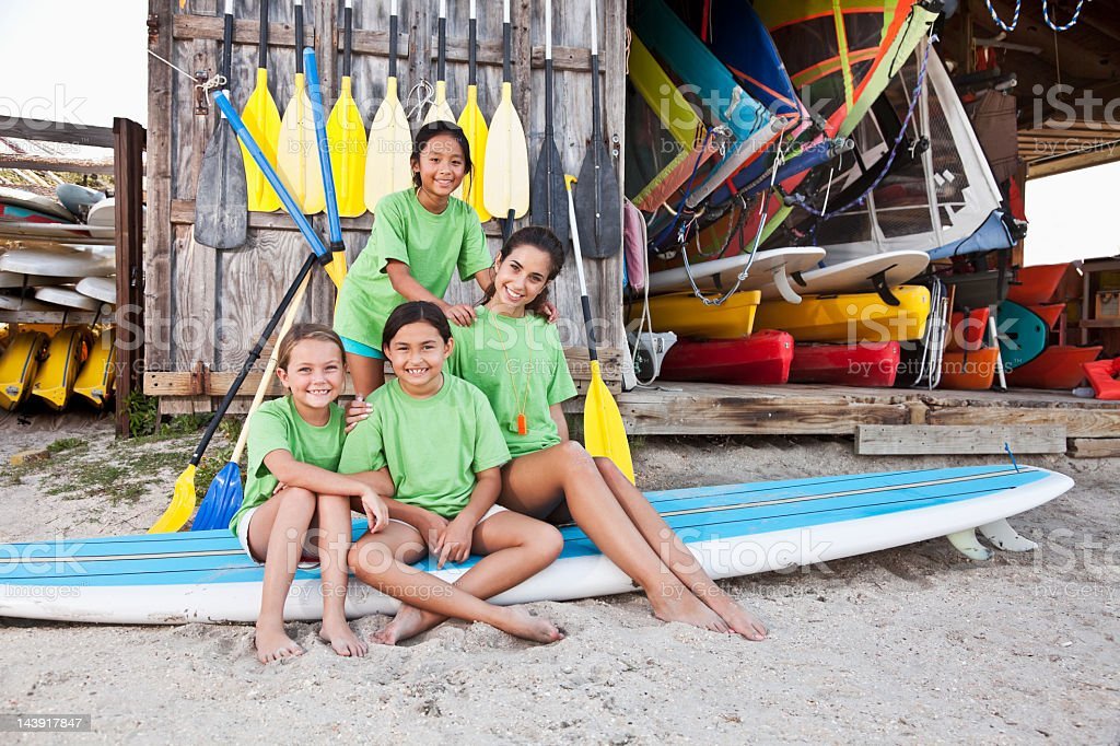Girls in front of water sports equipment shack royalty-free stock photo