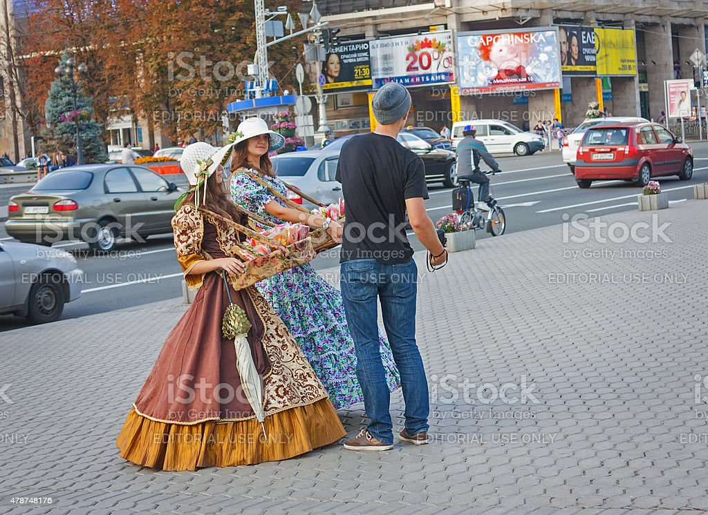 Girls in historical costumes sell sweets for tourists stock photo