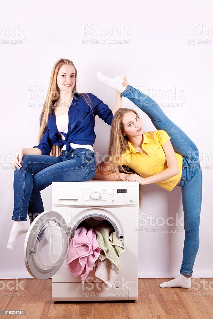Girls in jeans sitting on the washing machine stock photo