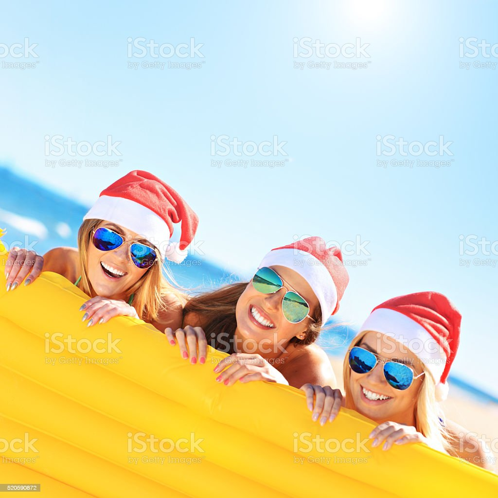 Girls in Santa's hats having fun on the beach stock photo
