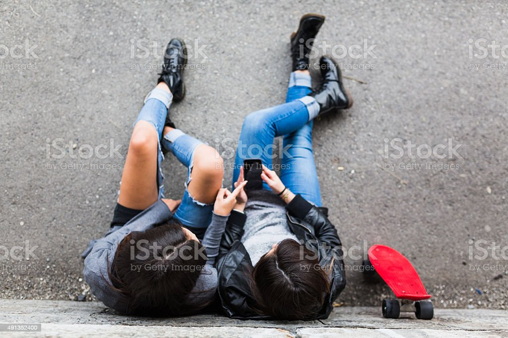 Girls in skatepark sharing smart phone. stock photo
