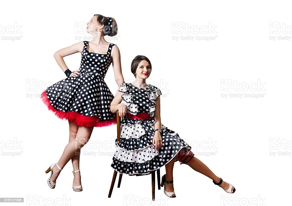 Girls in style of pin-up posing with chair stock photo