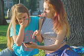 Girls in summer park watching videos and photos on smartphones