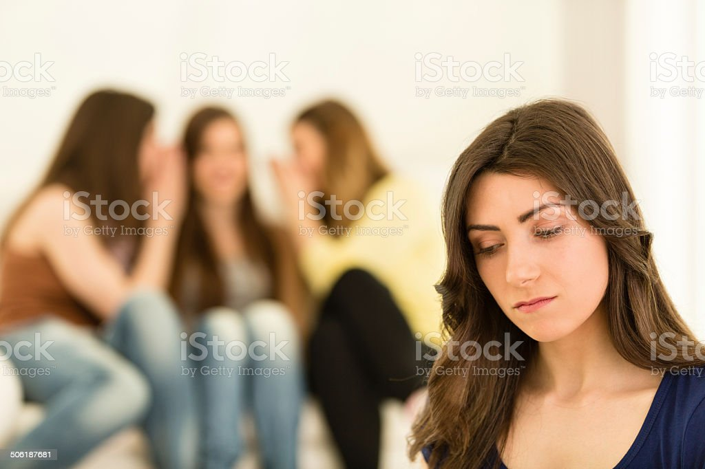 Girls in the background gossiping about another girl stock photo