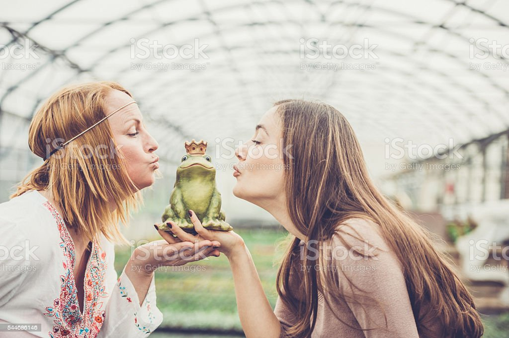 Girls kissing a frog stock photo