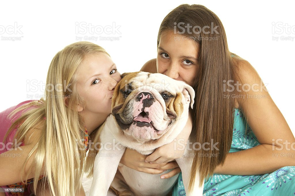 Girls Kissing Their Cute English Bulldog royalty-free stock photo