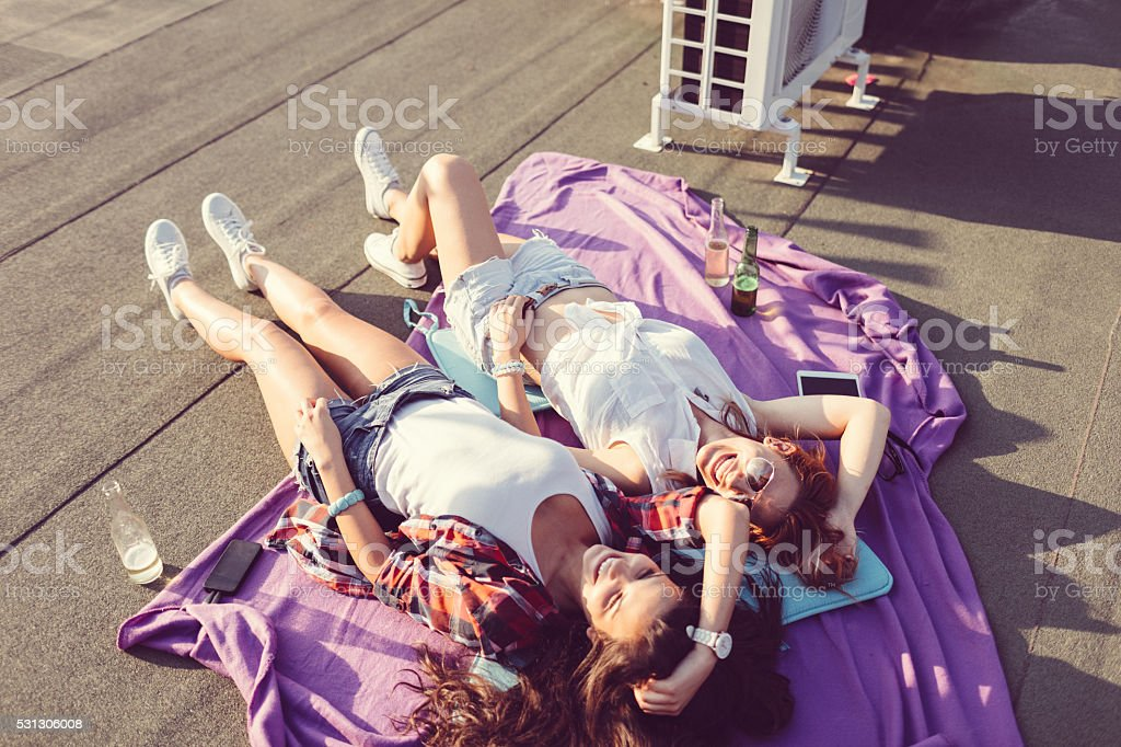 Girls laughing and sunbathing on the rooftop stock photo