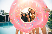 Girls laughing while holding a pool inflatable like a frame