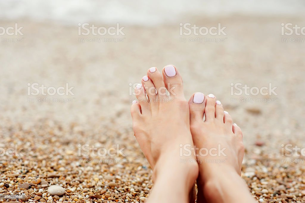 Girl's leg on colorful pebbles  the beach by the stock photo