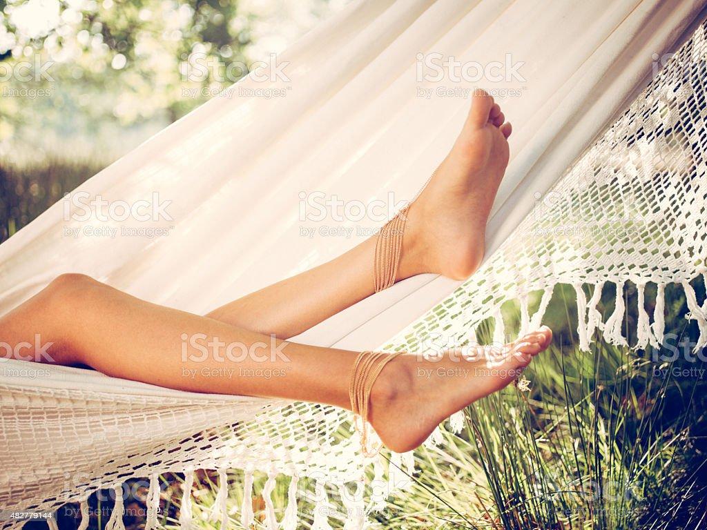 Girl's legs relaxing in a white hammock in summer stock photo