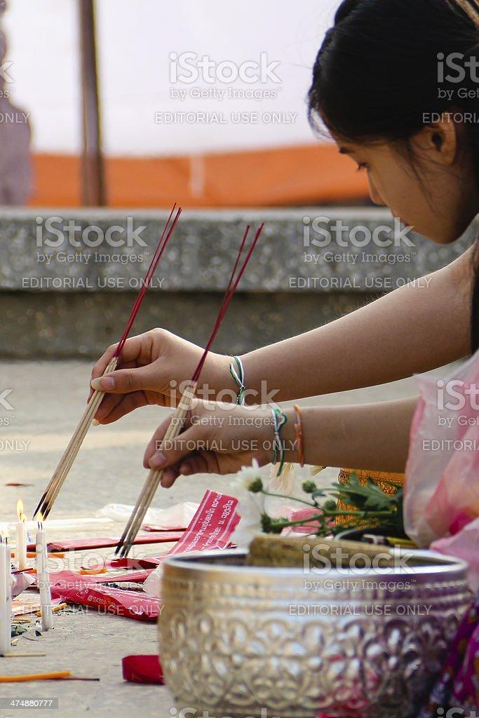 Girls lighting joss sticks stock photo