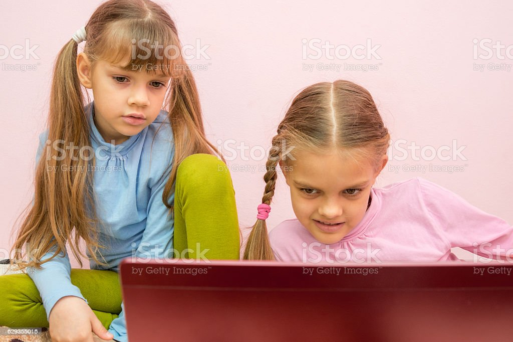 Girls look at the screen a bit tired of  view stock photo