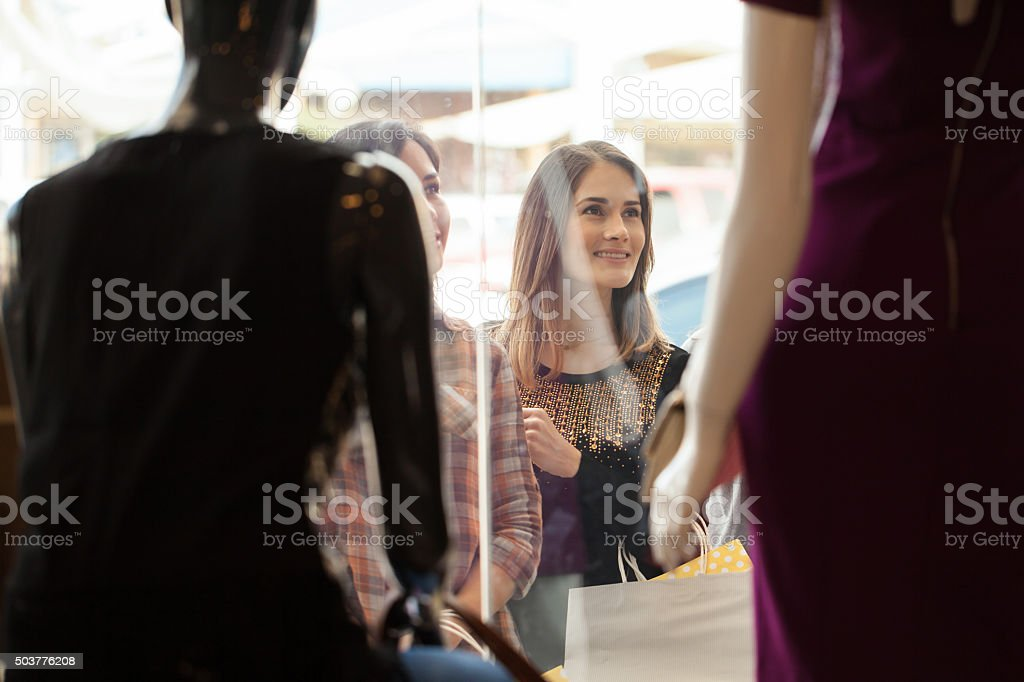 Girls looking at a clothing store display stock photo
