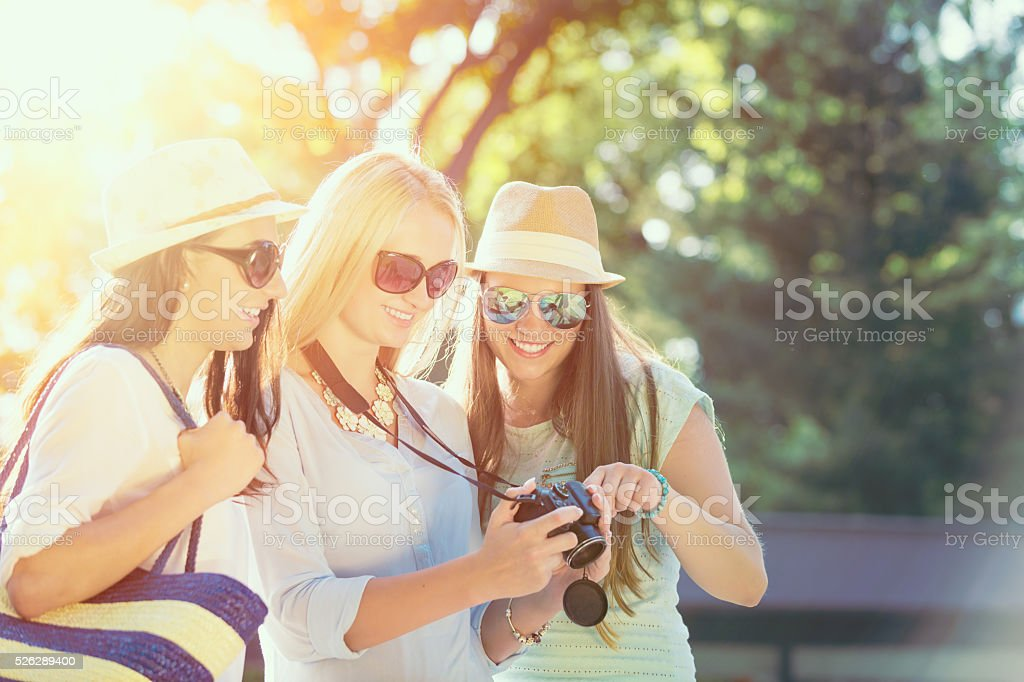 Girls looking at photos on their camera at summer holidays stock photo
