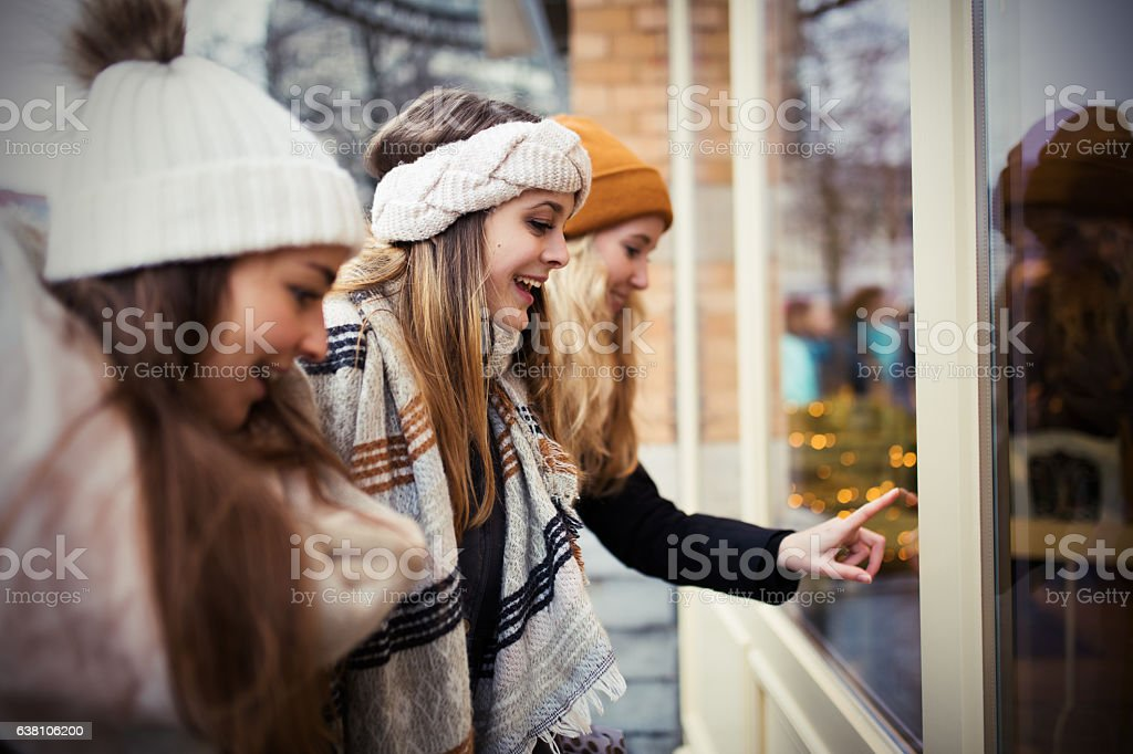 Girls looking at store window stock photo