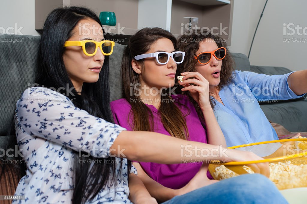 Girls looking scared while watching a movie stock photo
