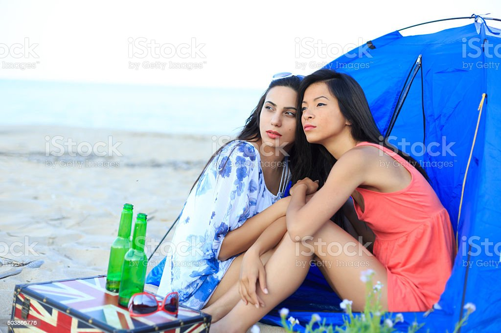 Girls looking the sky on beach stock photo