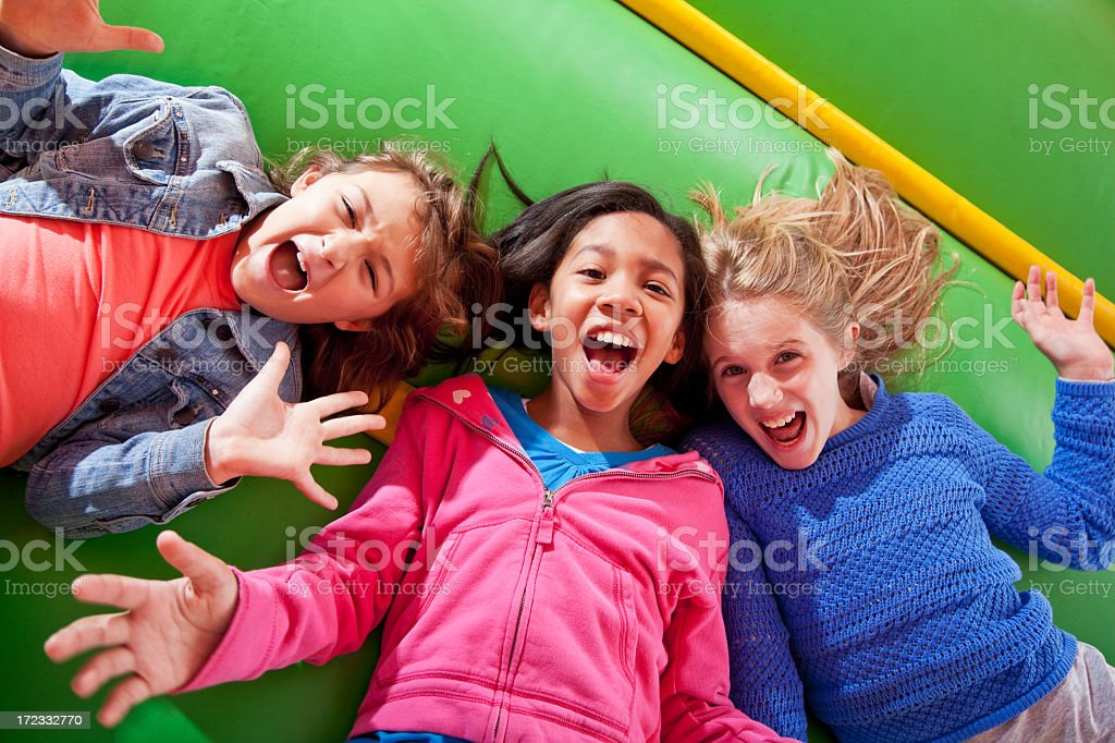 Girls lying down in bounce house stock photo