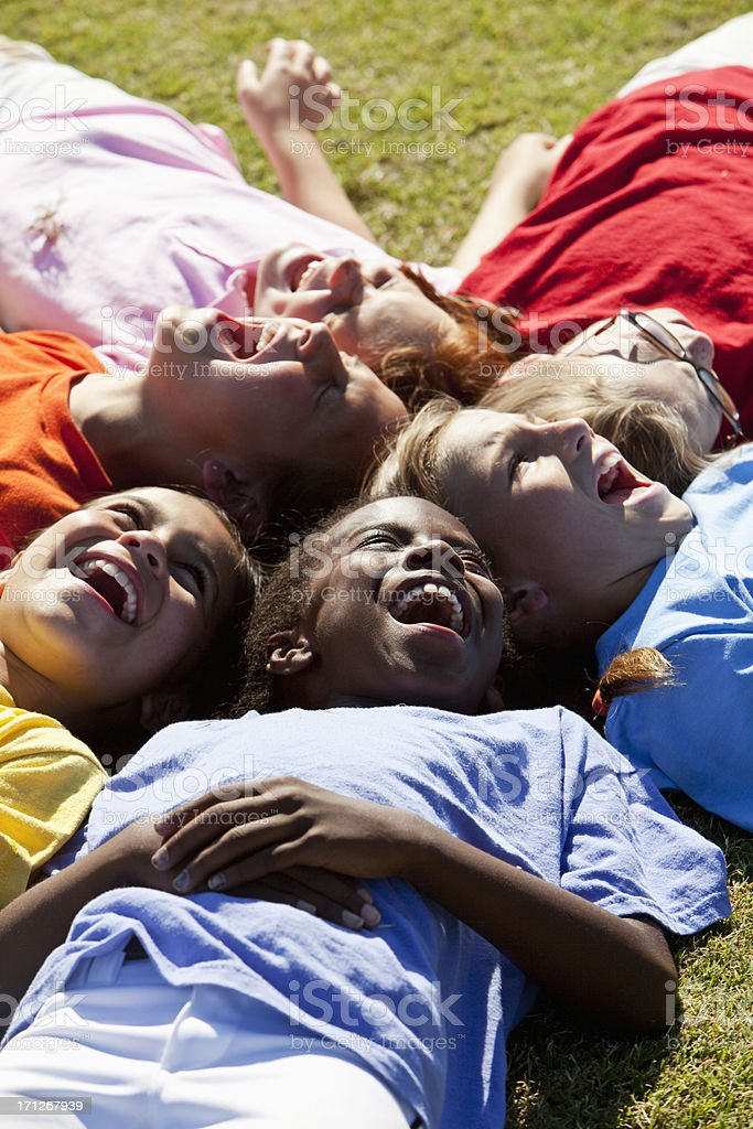 Girls lying in a circle looking up stock photo