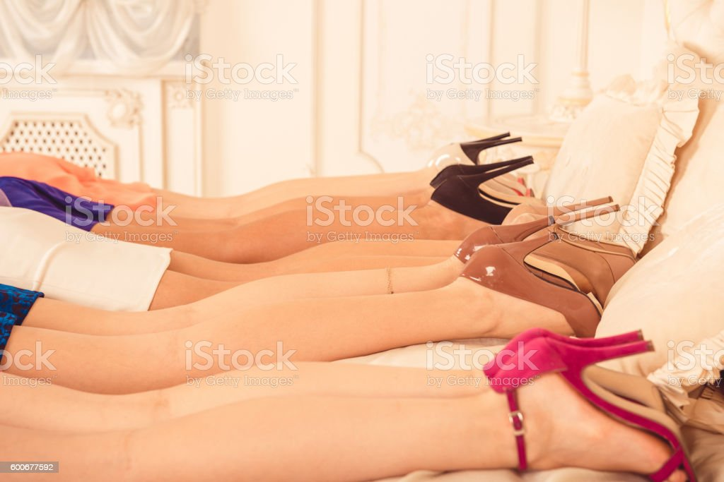 Girls lying on the bed and showing high heel shoes stock photo