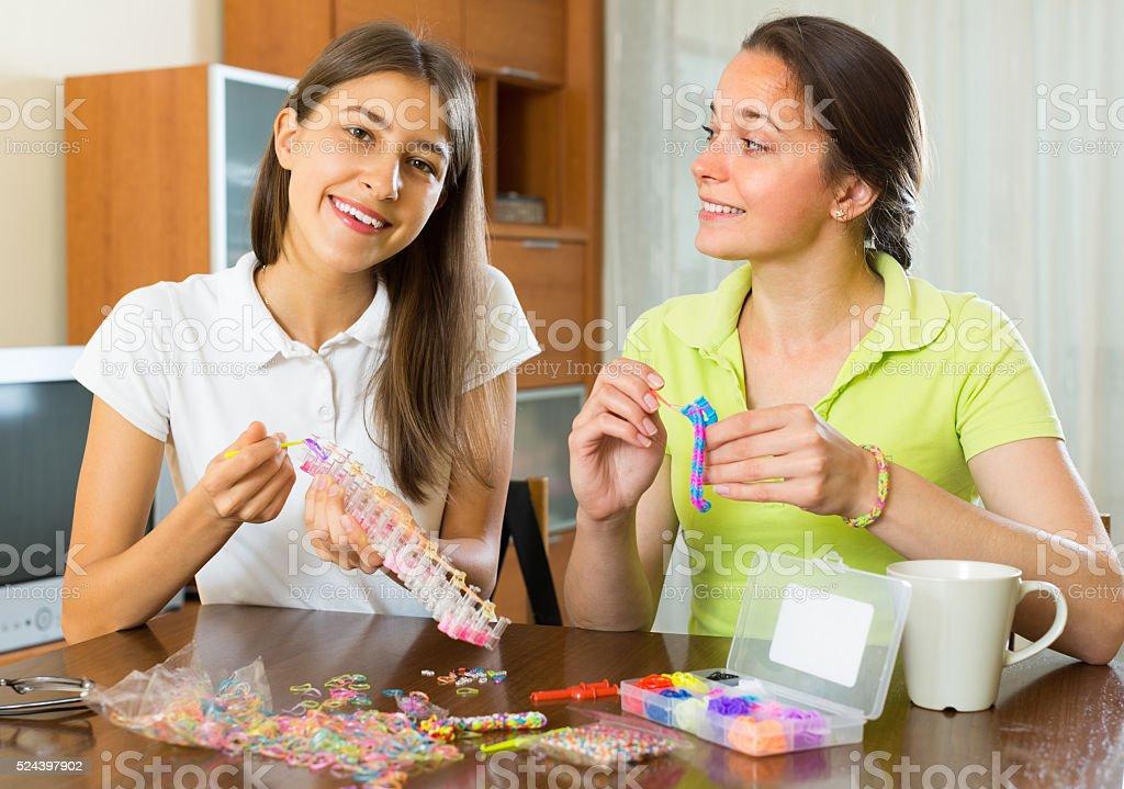 Girls making decorative bracelets stock photo
