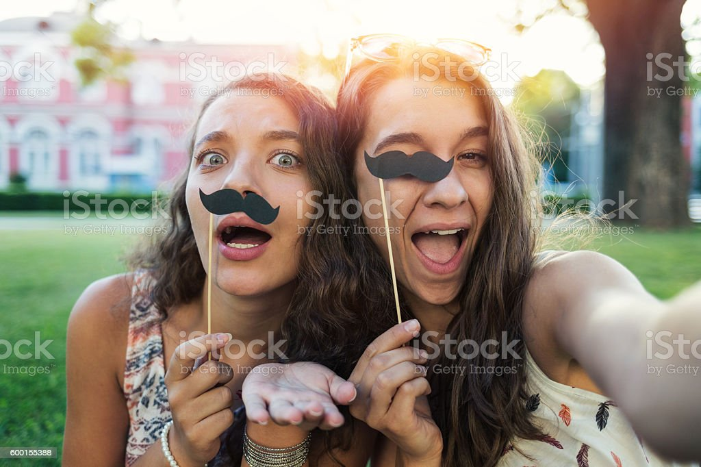 Girls making selfie with stache-on-a-stick stock photo