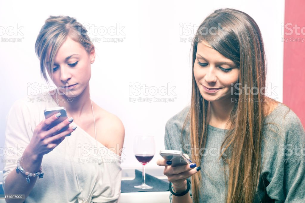 Girls messaging on mobile phone with friends royalty-free stock photo