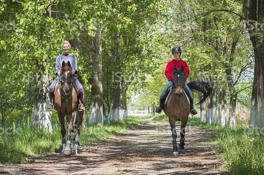 Girls on horseback riding stock photo