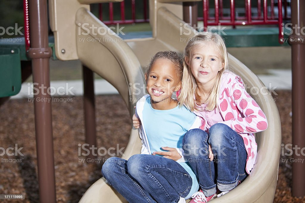 Girls on playground slide stock photo