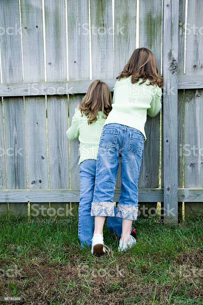 Girls Peaking Through the Fence stock photo