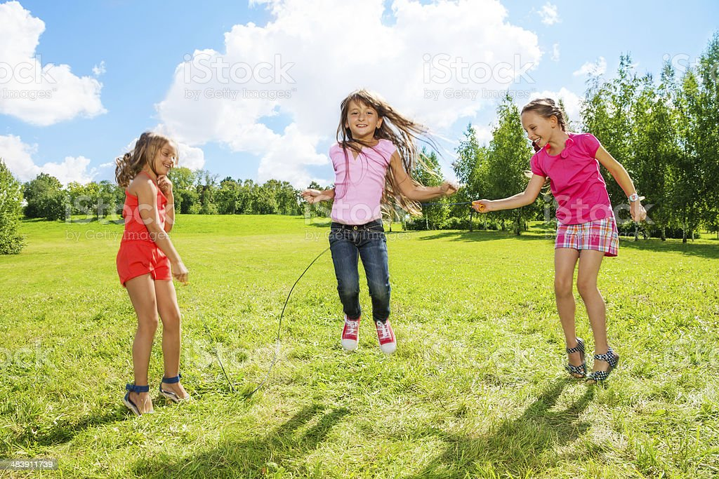 Girls play jumping over the rope stock photo