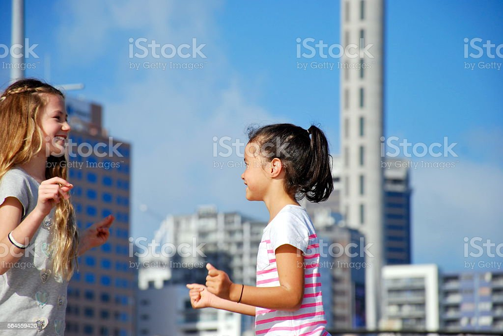 Girls Playing against Urban Scene stock photo