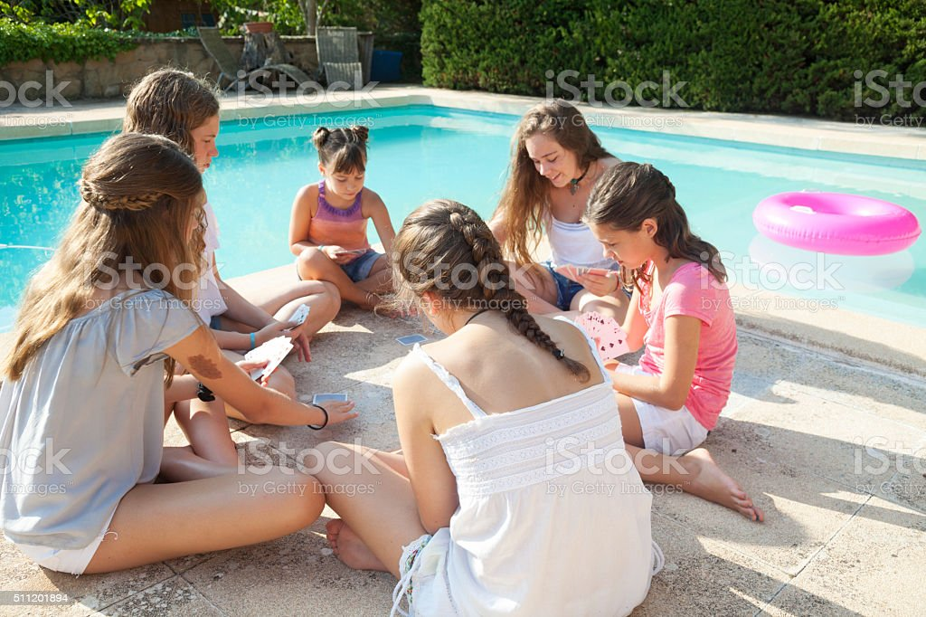 Girls playing cards in sumer by a pool stock photo
