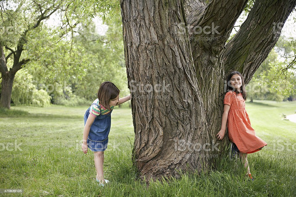 Girls Playing Hide And Seek By Tree stock photo