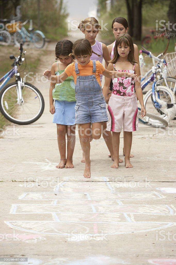 Girls (6-12) playing hopscotch stock photo