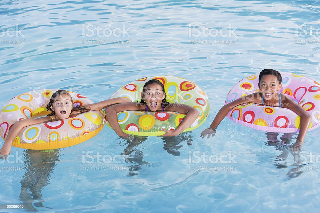 Girls playing in swimming pool. stock photo