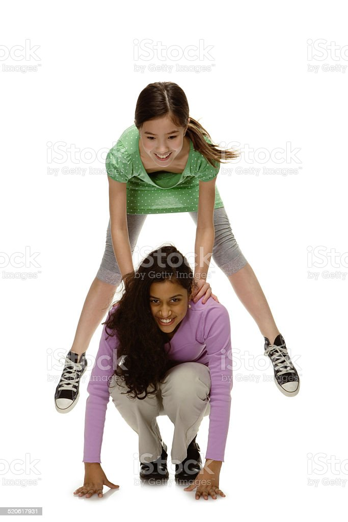 Girls (10-11) playing leap frog, smiling stock photo