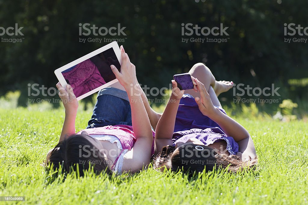 Girls Playing MP3 player and Digital Tablet stock photo