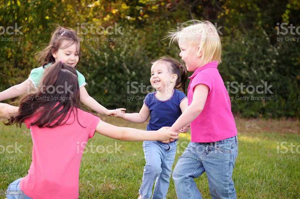 Girls Playing Ring-Around-the-Rosy Outside royalty-free stock photo