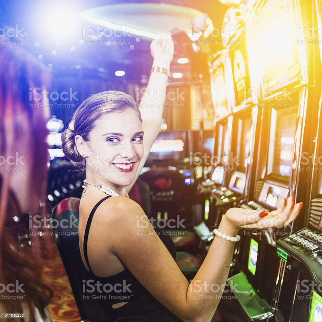 Girls playing slot machine in the casino stock photo