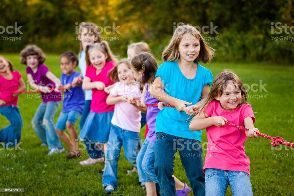 Girls Playing Tug-of-War Game Outside royalty-free stock photo