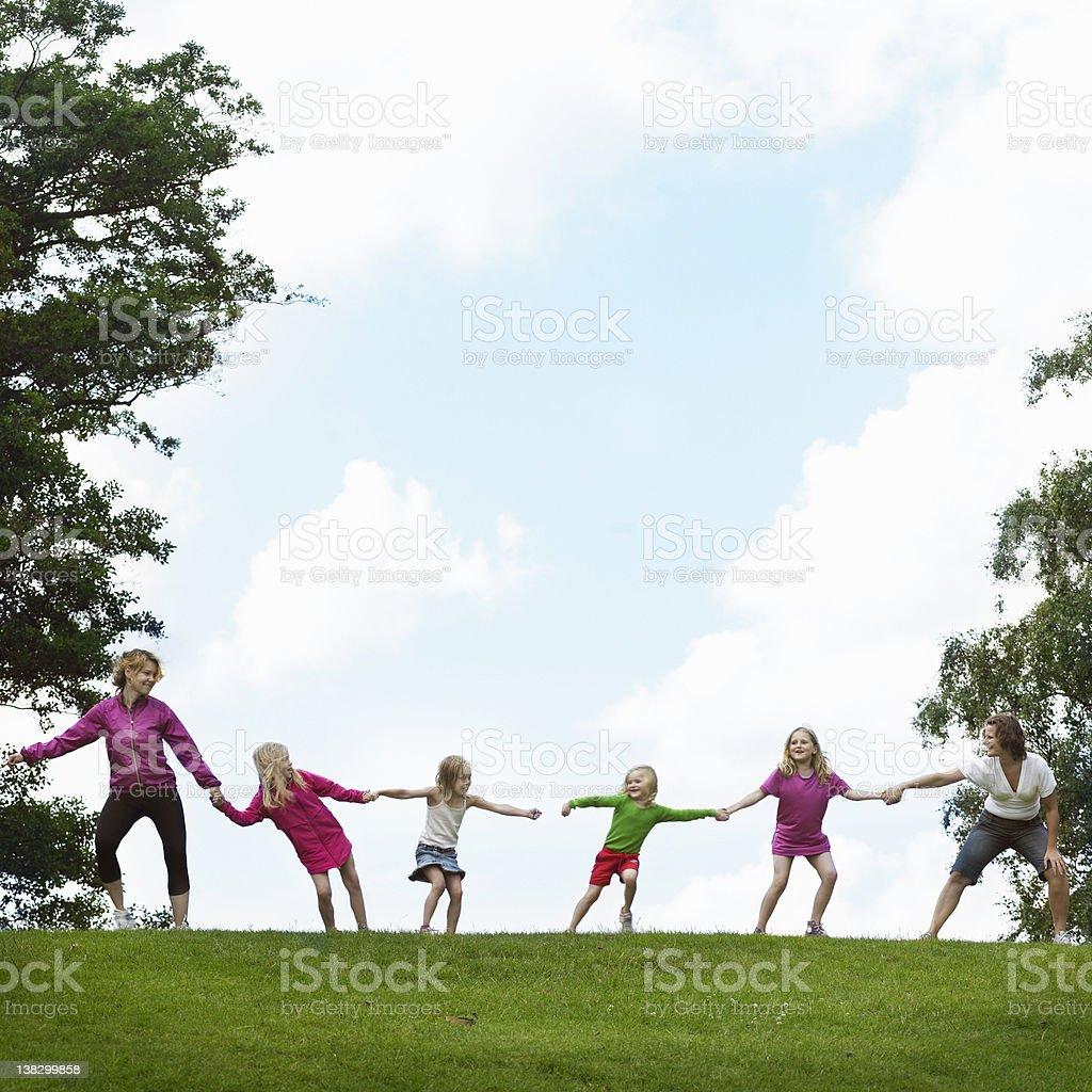 Girls playing tug-of-war in field stock photo