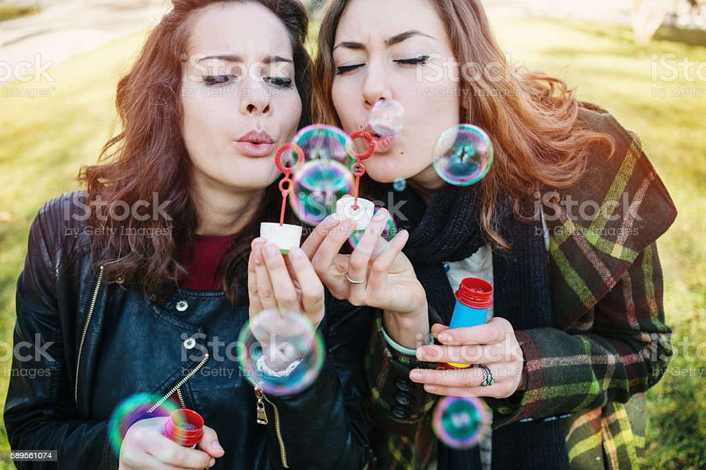 Girls playing with bubbles in the park stock photo