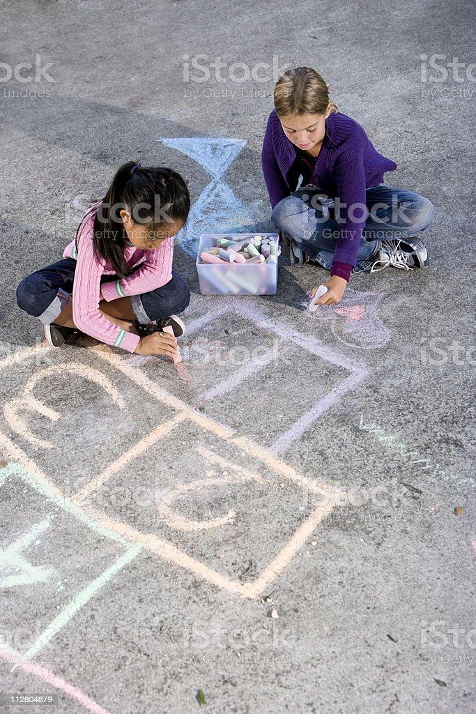 Girls playing with sidewalk chalk royalty-free stock photo