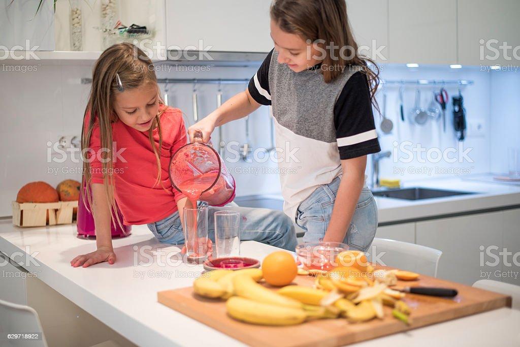 Girls preparing a smoothie stock photo