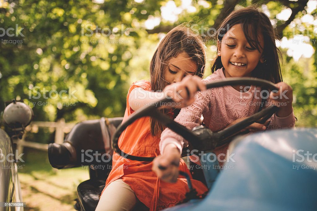 Girls pretending to drive a tractor on a sunny farm stock photo