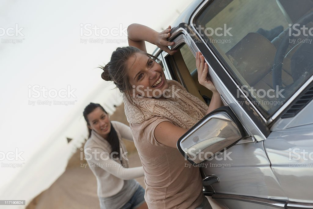 Girls pushing car stock photo