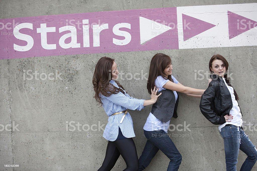 Girls pushing friend from back having fun royalty-free stock photo