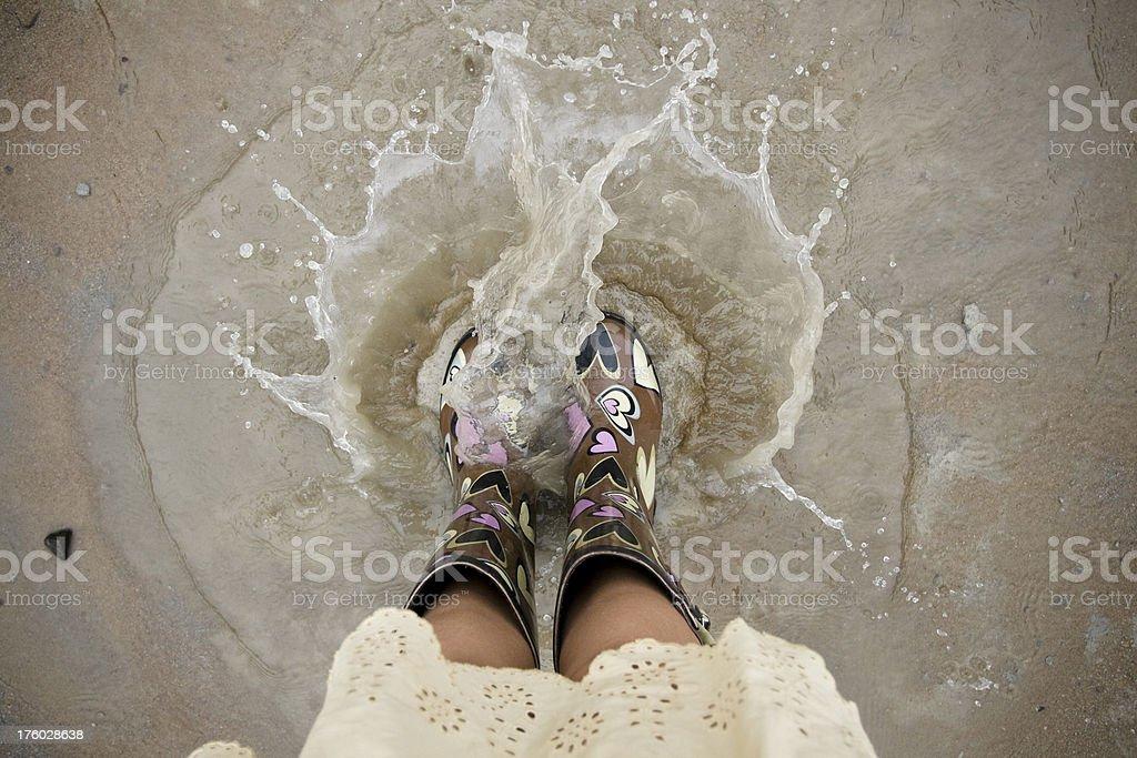 Girl's Rain Boots Splashing in the Mud stock photo